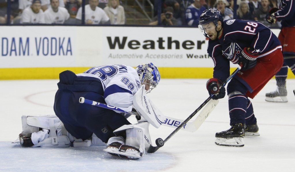 Tampa Bay Lightning's Andrei Vasilevskiy, left, of Russia, makes a save against Columbus Blue Jackets' Oliver Bjorkstrand, of Denmark, during the seco