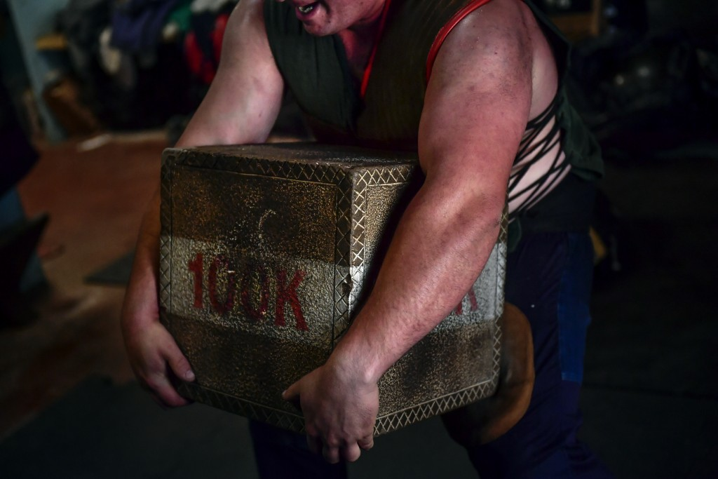In this Wednesday April 10, 2019 photo, Inigo Eizagirre, 24, a basque stone lifter, holds a 100 kilograms stone during a training session in the basqu