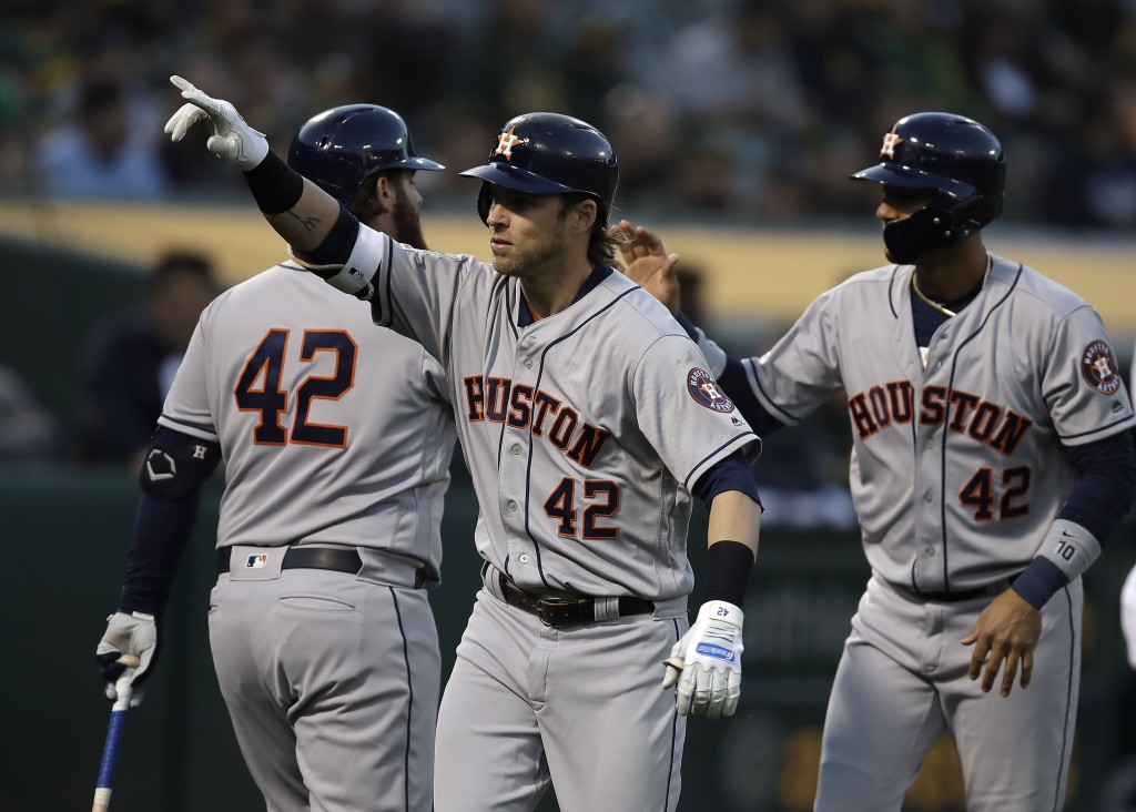 Houston Astros' Josh Reddick, center, celebrates after hitting a two-run home run off Oakland Athletics' Marco Estrada in the second inning of a baseb