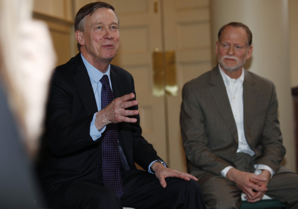 Democratic presidential hopeful John Hickenlooper, left, speaks as Michael Davis, back, look on during a meeting with survivors of victims of mass sho
