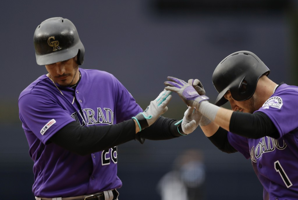 Colorado Rockies' Nolan Arenado, left, is greeted by Garrett Hampson after hitting a two-run home run during the first inning of the team's baseball g