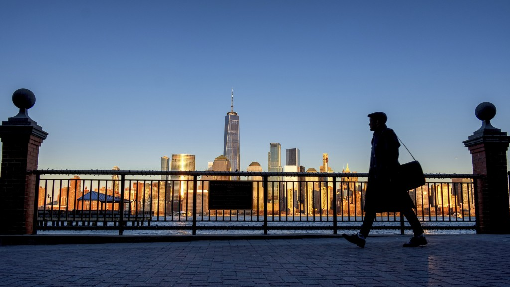 FILE - In this March 26, 2019 file photo, an evening commuter is silhouetted against the glistening New York City skyline at sunset as he walks along