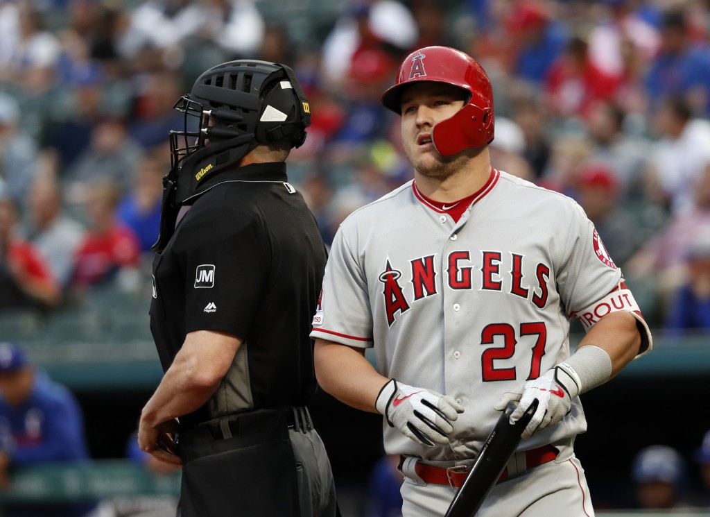 Los Angeles Angels' Mike Trout (27) walks behind the plate and umpire Carlos Torres after swinging at a pitch from Texas Rangers' Mike Minor during th