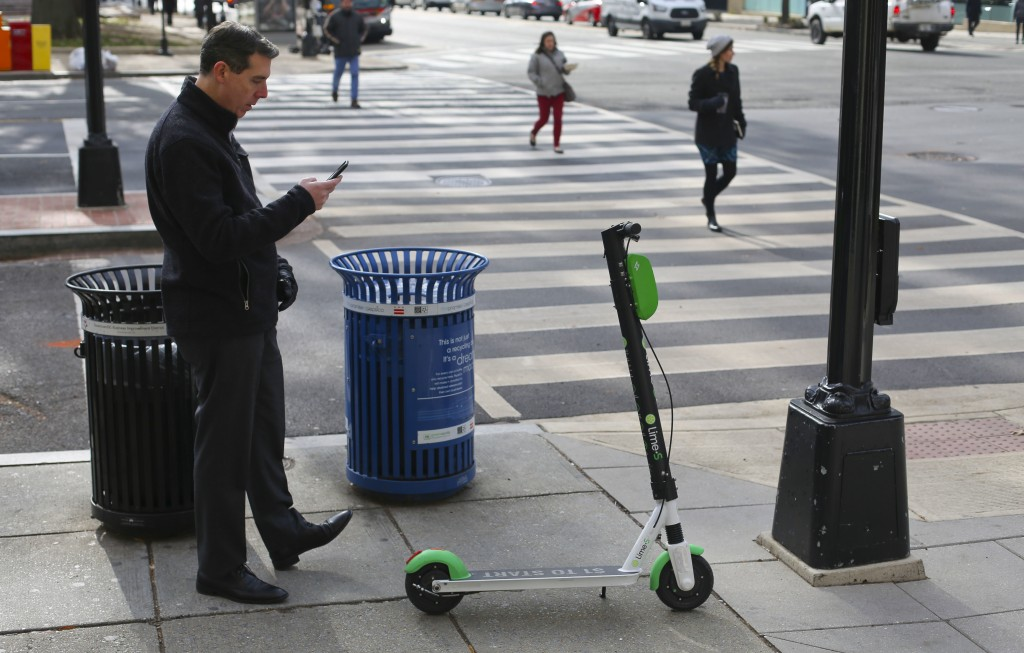 In this Dec. 6, 2018, photo a Lime scooter customer uses his mobile app to lock up his scooter on the sidewalk after finishing his trip in downtown Wa