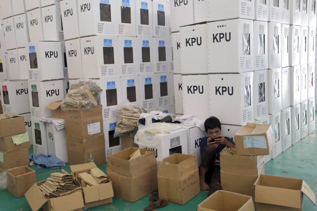 In this Wednesday, April 10, 2019, photo, an Indonesian electoral worker takes a break among ballot boxes to be distributed to polling stations in Jak