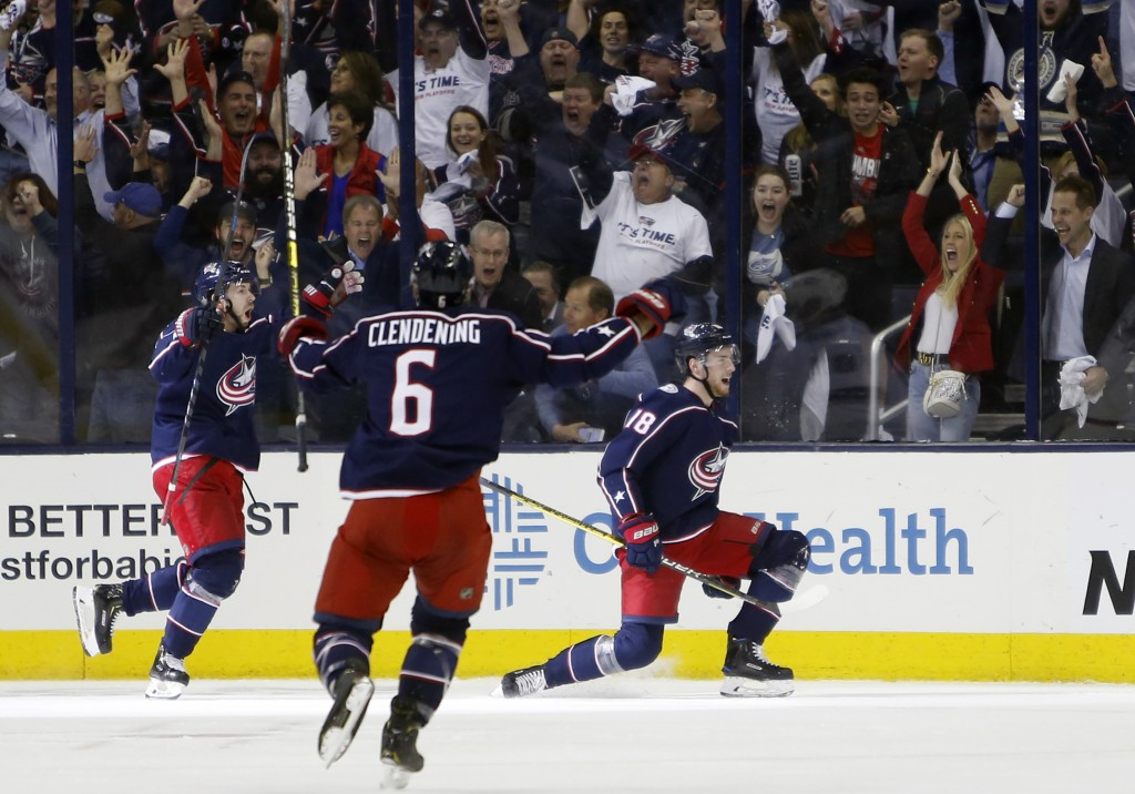 Columbus Blue Jackets' Pierre-Luc Dubois, right, celebrates his goal against the Tampa Bay Lightning with teammates Oliver Bjorkstrand, left, of Denma