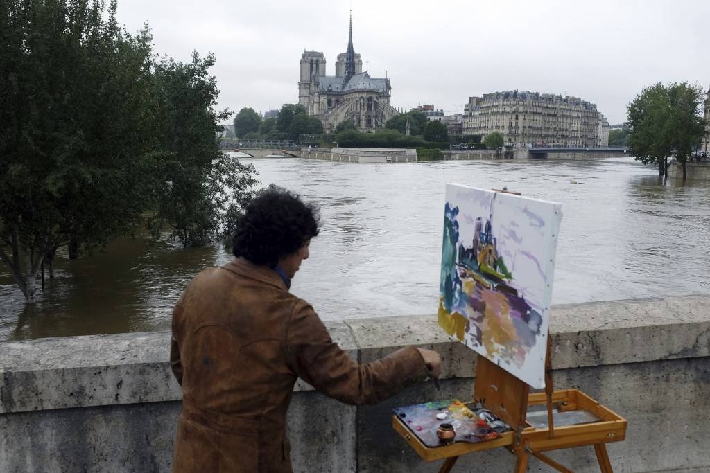 FILE - In this Friday, June 3, 2016 file photo, a man paints the Notre Dame cathedral surrounded by the flooding Seine river in Paris, France. The Got