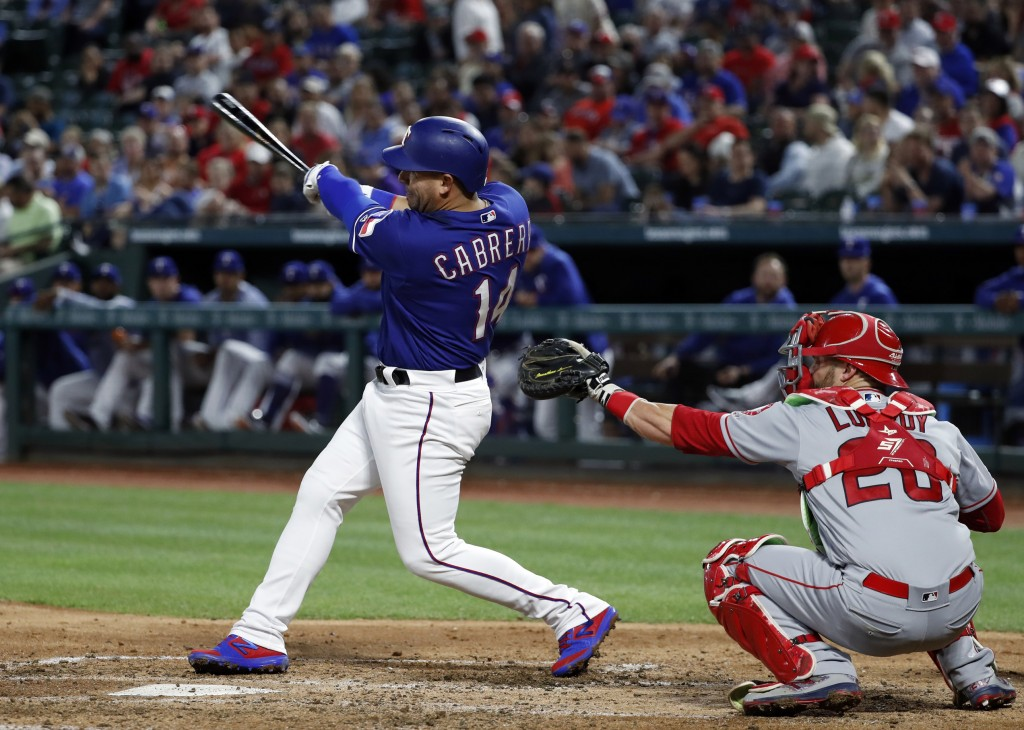 Texas Rangers' Asdrubal Cabrera follows through on a two-run home run in front of Los Angeles Angels catcher Jonathan Lucroy during the fourth inning