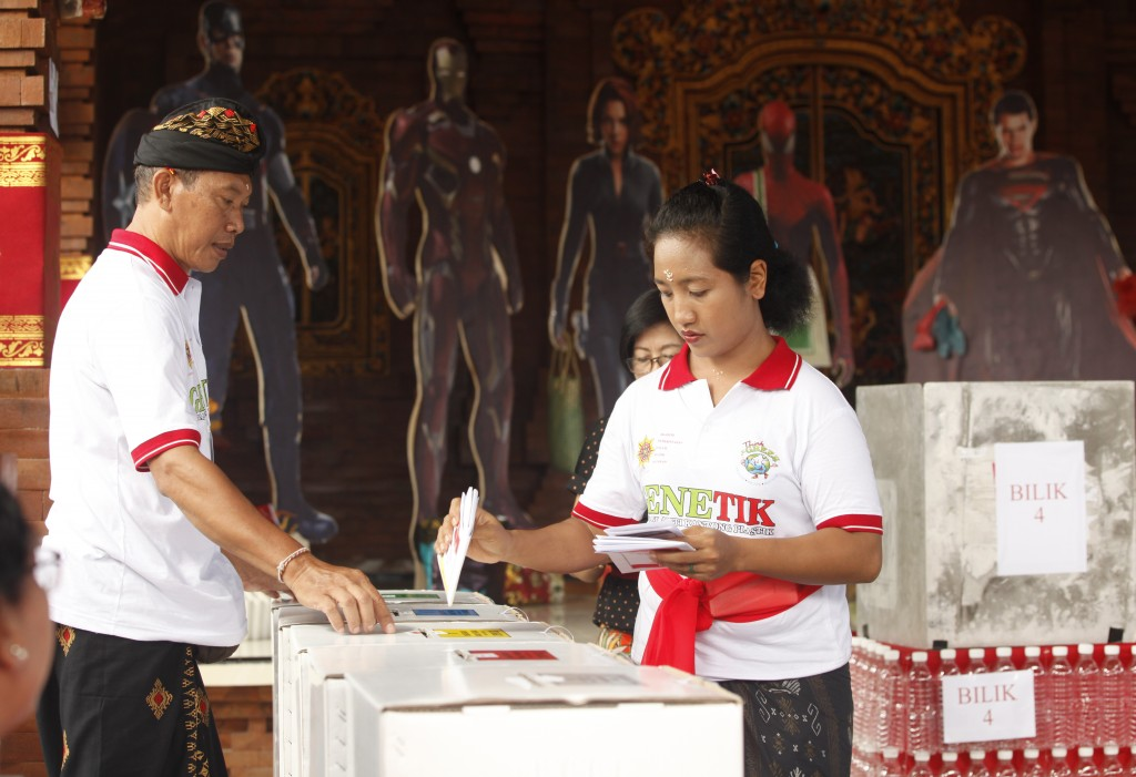 A woman casts her ballot at a polling station during election in Bali, Indonesia on Wednesday, April 17, 2019. Voting is underway in Indonesia's presi