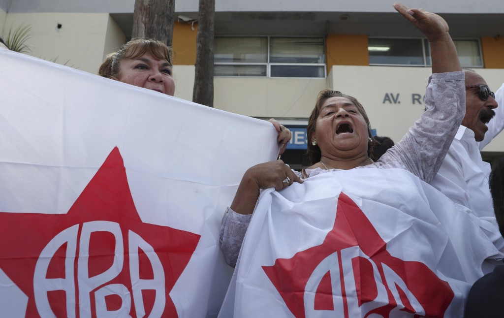 Supporters of former Peruvian President Alan Garcia gather outside the hospital where Garcia was taken after he shot himself, in Lima, Peru, Wednesday