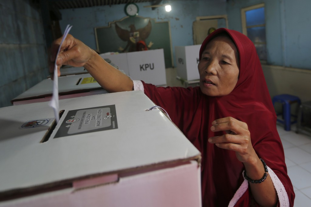 A woman casts her ballot at a polling station during the election in Jakarta, Indonesia, Wednesday, April 17, 2019. The Indonesian presidential electi...