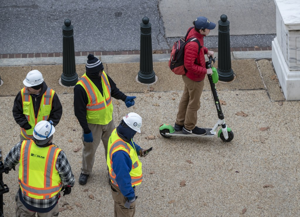 In this Dec. 5, 2018, photo a rider maneuvers a Lime brand electric scooter on a sidewalk past workers on Capitol Hill in Washington. Electric scooter