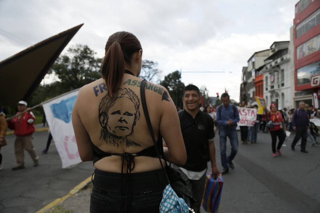 A protester wearing a Julian Assange image on her back protests the policies of President Lenin Moreno's government as demonstrators march to the pres