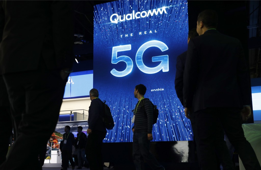 FILE- In this Jan. 9, 2019, file photo a sign advertises 5G at the Qualcomm booth at CES International in Las Vegas. Apple and mobile chip maker Qualc...