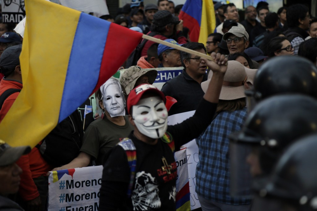 People wearing Julian Assange and Guy Fawkes masks protest the policies of President Lenin Moreno's government as they march to the presidential palac