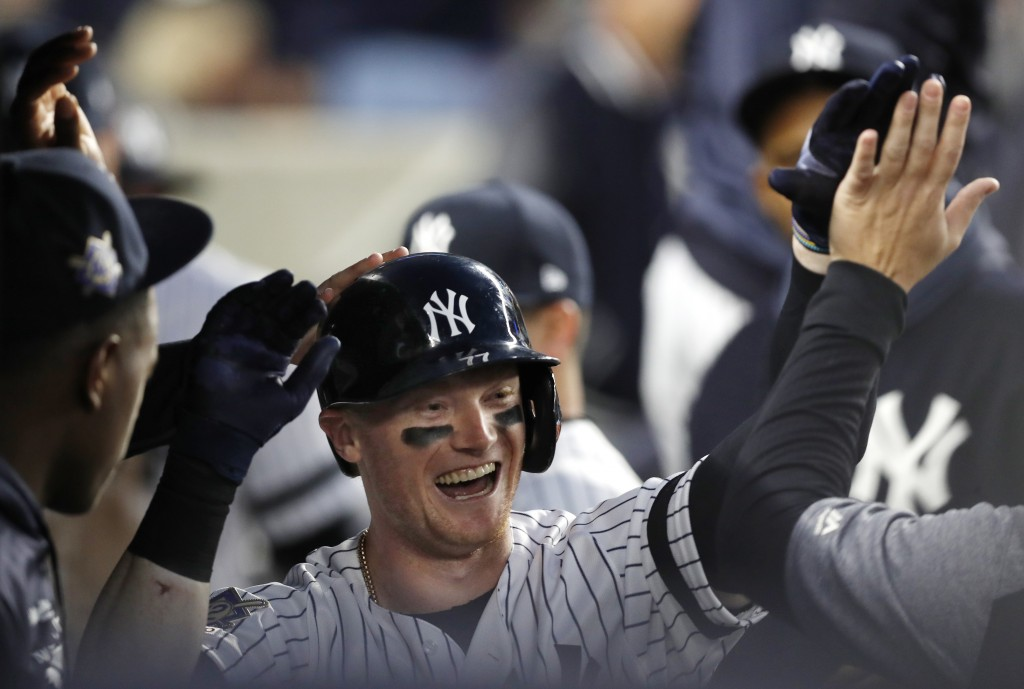 New York Yankees' Clint Frazier is congratulated in the dugout after hitting a solo home run off Boston Red Sox starting pitcher Chris Sale during the