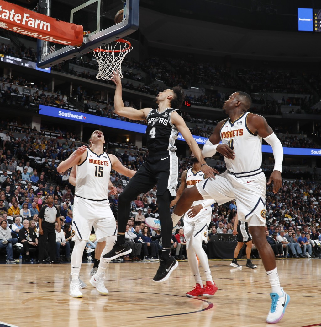 San Antonio Spurs guard Derrick White, center, shoots between Denver Nuggets center Nikola Jokic, left, and forward Paul Millsap in the first half of ...