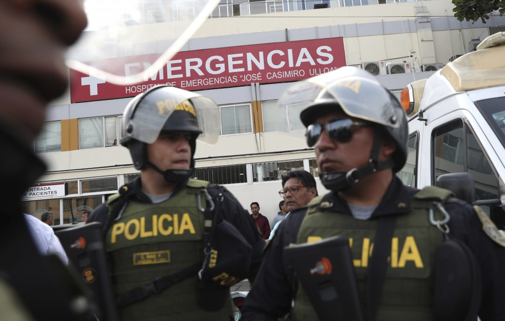 Police officers stand guard at the emergency entrance of the Casimiro Ulloa hospital where former Peruvian President Alan Garcia was taken after he sh