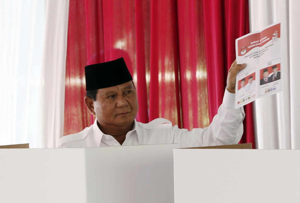 Indonesian presidential candidate Prabowo Subianto shows his ballot paper before voting during the presidential election at a polling station in Bogor