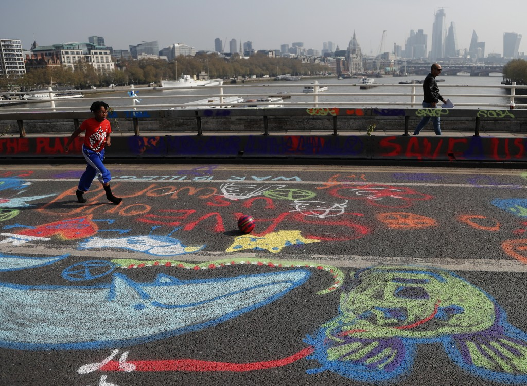 A boy plays football on graffiti drawn by protestors who blocked Waterloo Bridge in London, Wednesday, April 17, 2019, with the River Thames and the c