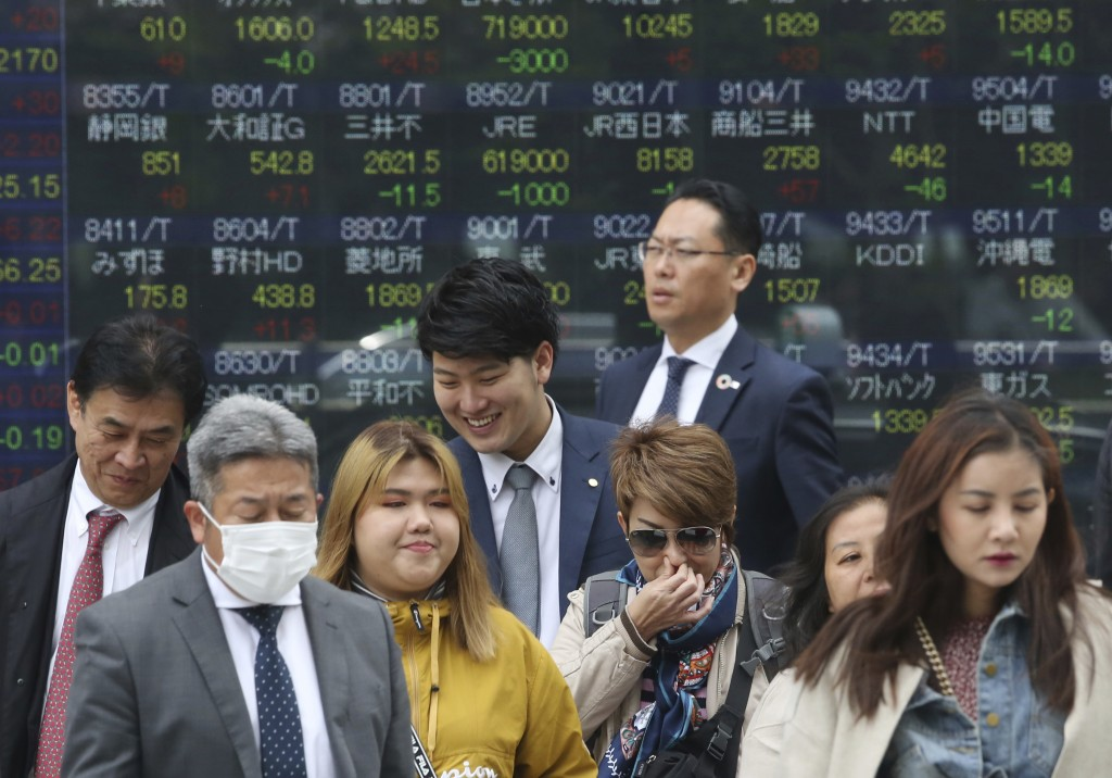 People stand in front of an electronic stock board of a securities firm in Tokyo, Wednesday, April 17, 2019. Shares were mixed in a narrow range Wedne