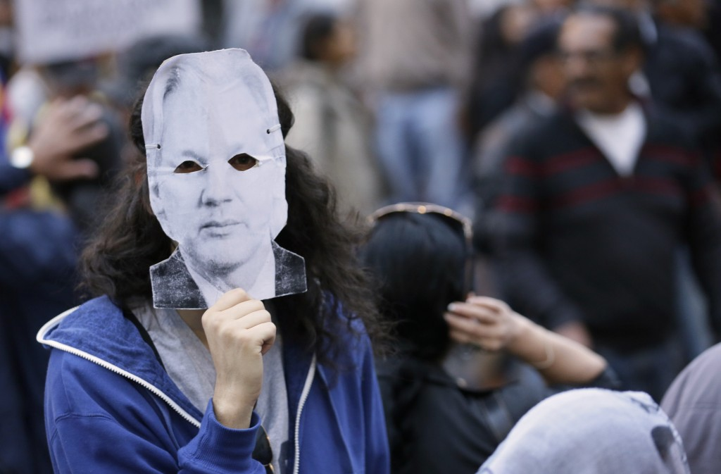 A protester wearing a Julian Assange mask protests the policies of President Lenin Moreno's government as they march to the presidential palace in Qui