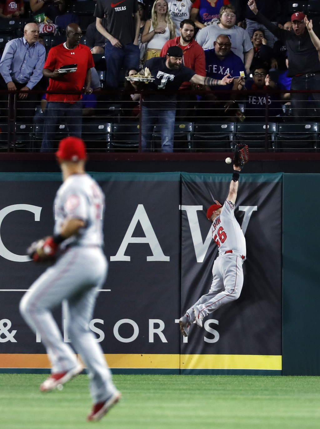 Los Angeles Angels second baseman Tommy La Stella watches as the ball glances off the glove of right fielder Kole Calhoun and falls behind the wall fo