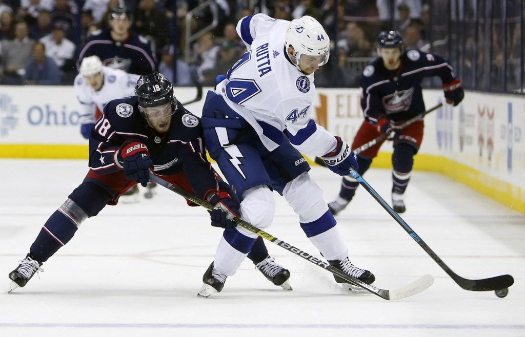 Columbus Blue Jackets' Pierre-Luc Dubois, left, and Tampa Bay Lightning's Jan Rutta, of the Czech Republic, fight for a loose puck during the second p...