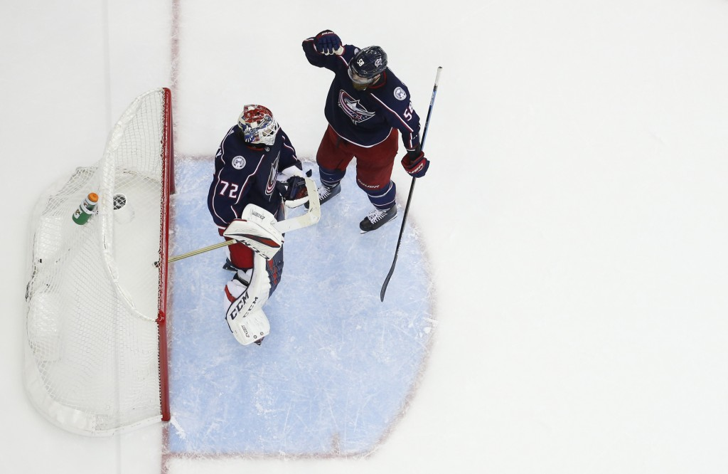 Columbus Blue Jackets' Sergei Bobrovsky, of Russia, and David Savard celebrate their win over the Tampa Bay Lightning in Game 4 of an NHL hockey first...