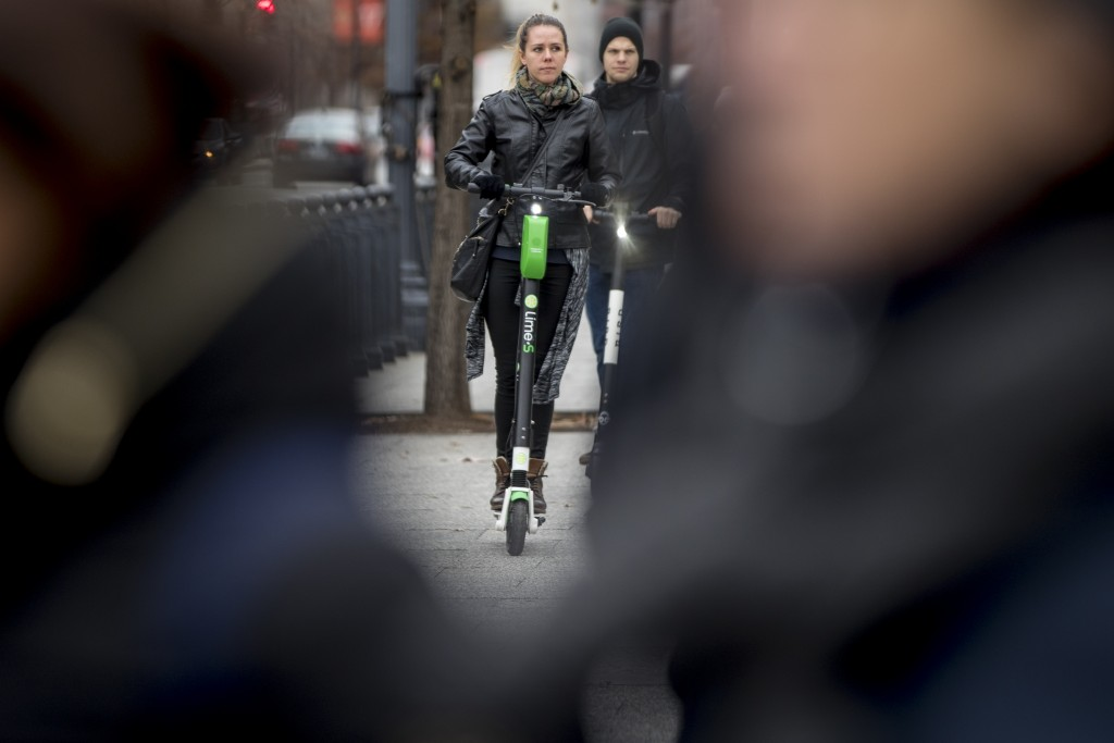 In this Dec. 4, 2018, photo a couple rides scooters near the White House in Washington. Electric scooters are overtaking station-based bicycles as the