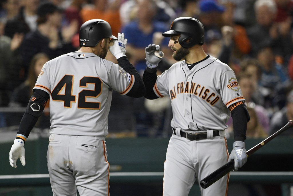San Francisco Giants' Evan Longoria, left, celebrates his home run with Kevin Pillar, right, during the fifth inning of a baseball game against the Wa