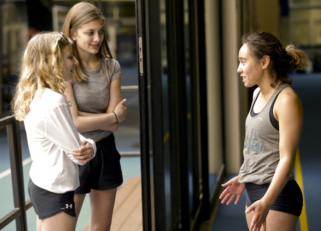 In this Thursday, April 11, 2019, photo, Gymnast Katelyn Ohashi, right, greets gymnasts and fans, Catelyn Zack, 15, left, and Greta Haroldson, 15, bot