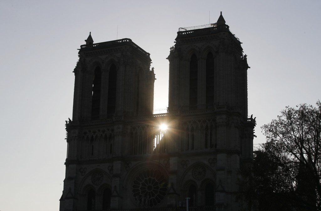 The sun rises between the two towers of Notre Dame cathedral Wednesday, April 17, 2019 in Paris. Nearly $1 billion has already poured in from ordinary