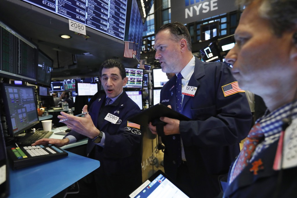 FILE - In this April 12, 2019, file photo specialist Peter Mazza, left, and trader Jonathan Corpina, center, work on the floor of the New York Stock E