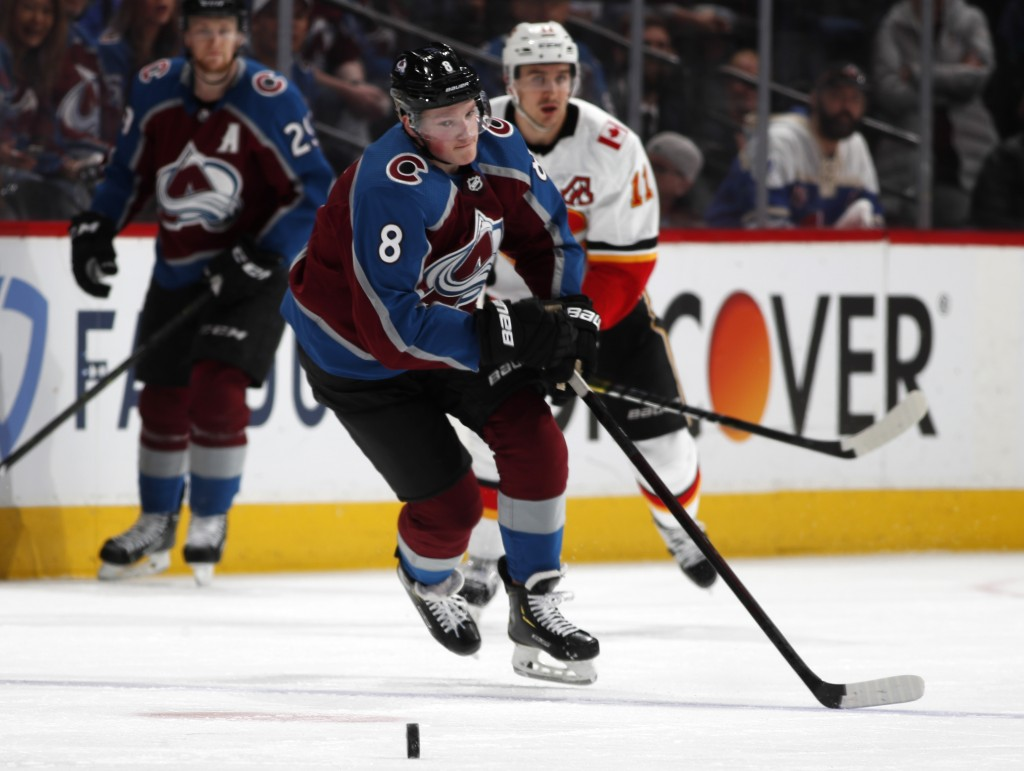 Colorado Avalanche defenseman Cale Makar, front, loses control of a pass as Calgary Flames center Mikael Backlund defends in the second period of Game...
