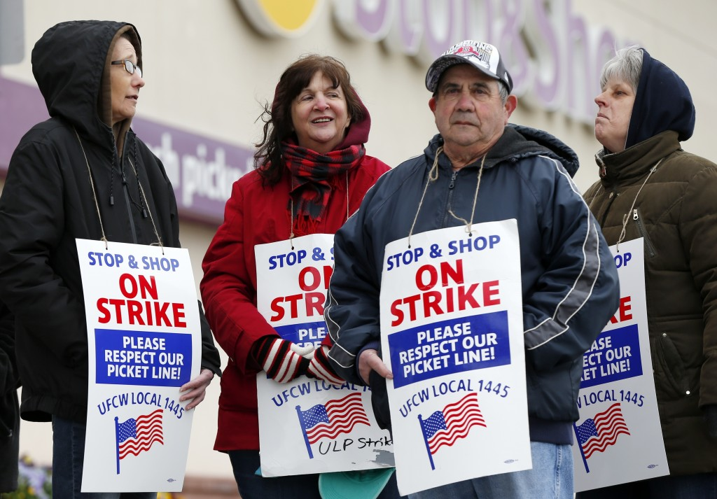 Striking workers stand on a picket line outside the Stop & Shop supermarket in Revere, Mass., Thursday, April 18, 2019. Some Jewish families in southe...
