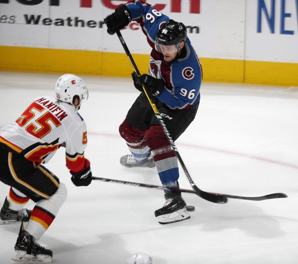 Calgary Flames defenseman Noah Hanifin, left, pokes the puck away from Colorado Avalanche right wing Mikko Rantanen during the first period of Game 4 ...