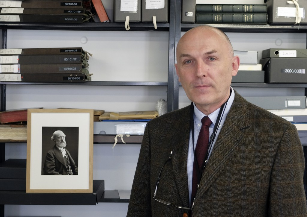 Jean-Charles Forgeret poses next to photograph of Eugene Emmanuel Viollet-le-Duc, the renowned architect who designed the spire that was added to the