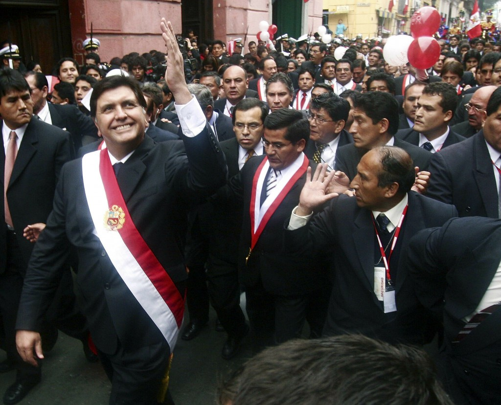 FILE - In this July 28, 2006 file photo, Peruvian President Alan García waves to a crowd after his swearing-in ceremony while he walks through the str
