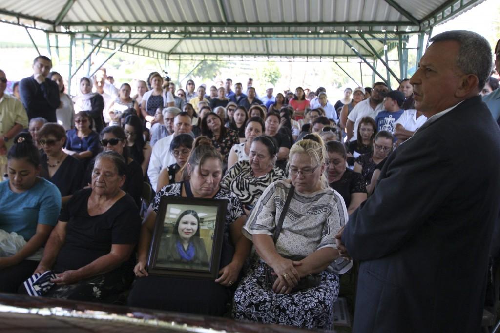 FILE - In this April 17, 2018 file photo, Demetrio Turcios, right, father of slain journalist Karla Turcios, addresses people attending Karla's funera