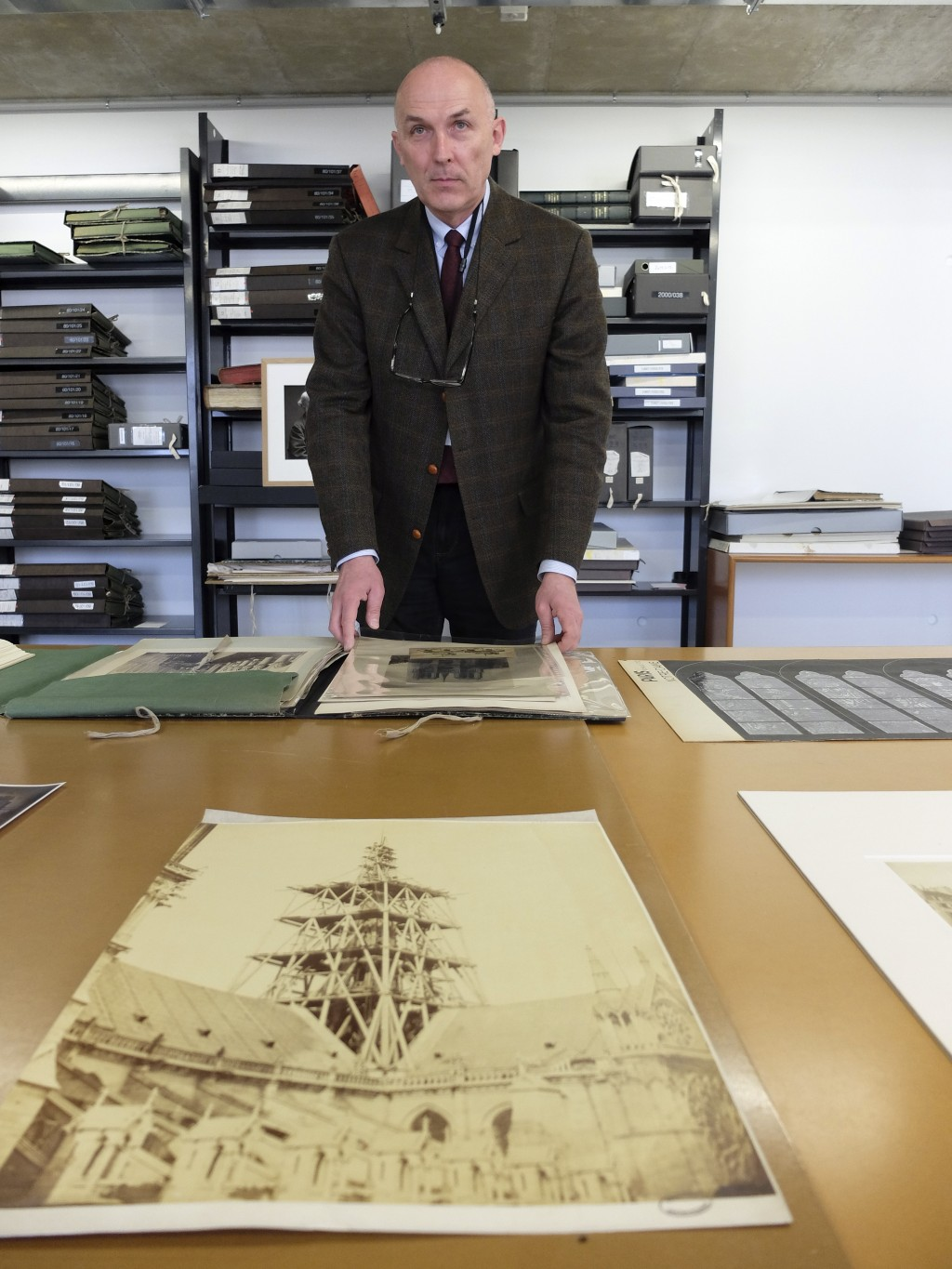 Jean-Charles Forgeret poses with archives documents related to Notre Dame cathedral in Charenton le Pont, outside Paris, Thursday, April 18, 2019. The