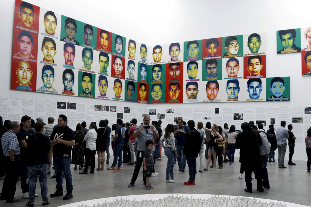 People stand under the portraits of 43 college students who went missing in 2014 in an apparent massacre, by Chinese concept artist and government cri