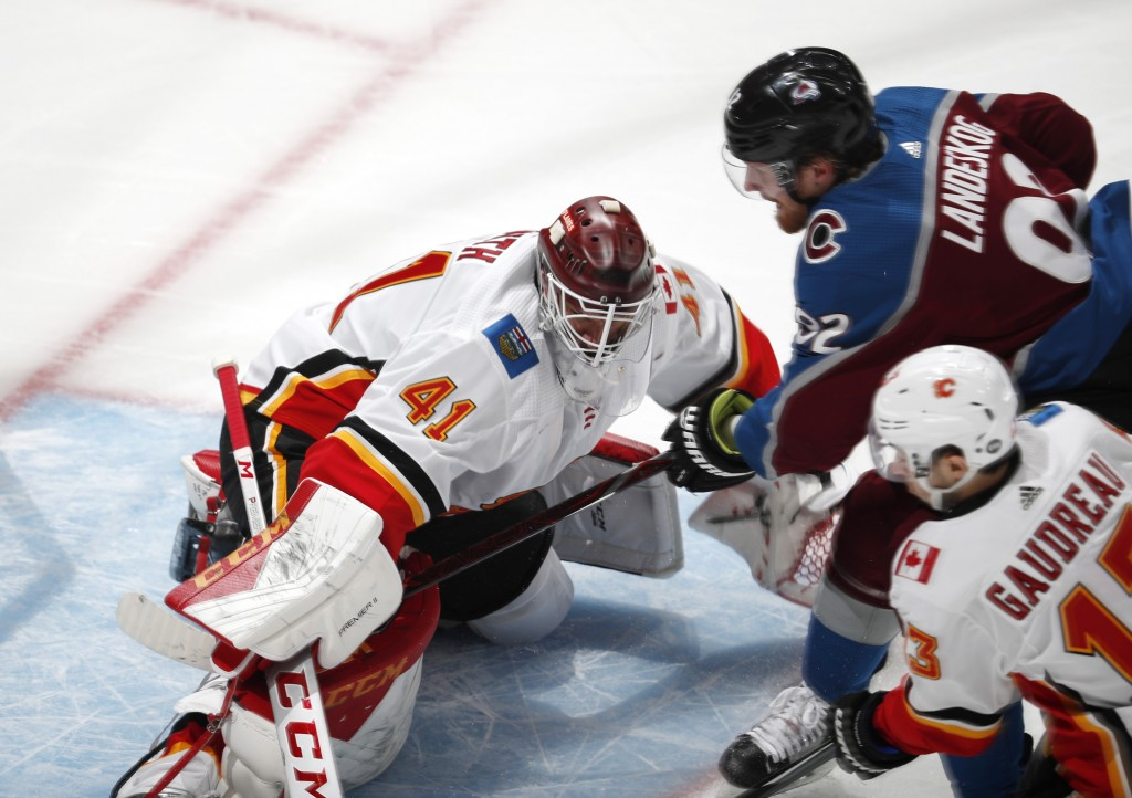 Calgary Flames goaltender Mike Smith, left, stops a shot by Colorado Avalanche left wing Gabriel Landeskog, back right, who drives by Calgary left win...
