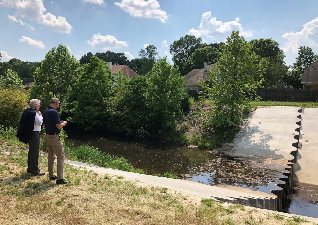 FILE - In this May 15, 2018 file photo, two men inspect a U.S. Army Corps of Engineers project to prevent erosion in an important storm sewage channel...