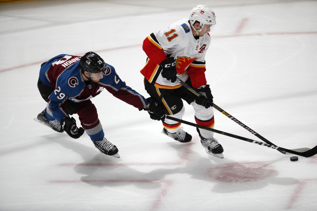 Colorado Avalanche center Nathan MacKinnon, left, reaches for the puck as Calgary Flames center Mikael Backlund moves down the ice during the first pe...