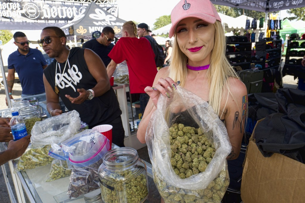 FILE - In this Saturday, April 21, 2018 file photo a bud tender offers attendees the latest products of cannabis at the High Times 420 SoCal Cannabis ...