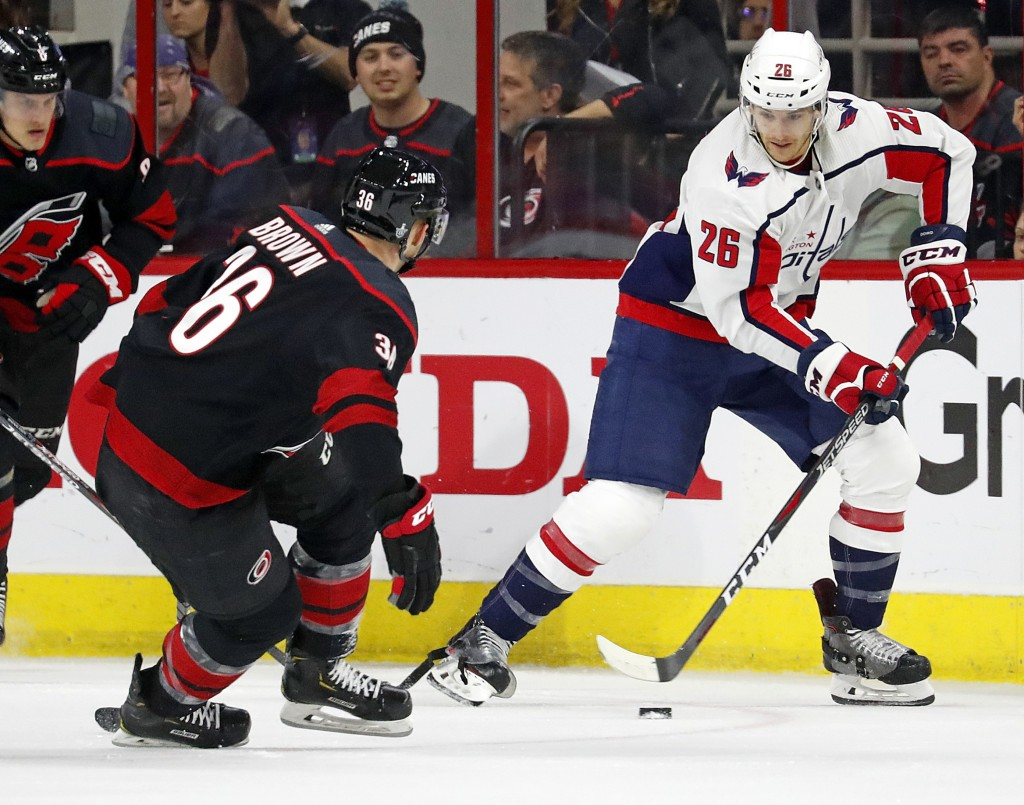 Washington Capitals' Nic Dowd (26) moves the puck as Carolina Hurricanes' Patrick Brown (36) defends during the first period of Game 4 of an NHL hocke