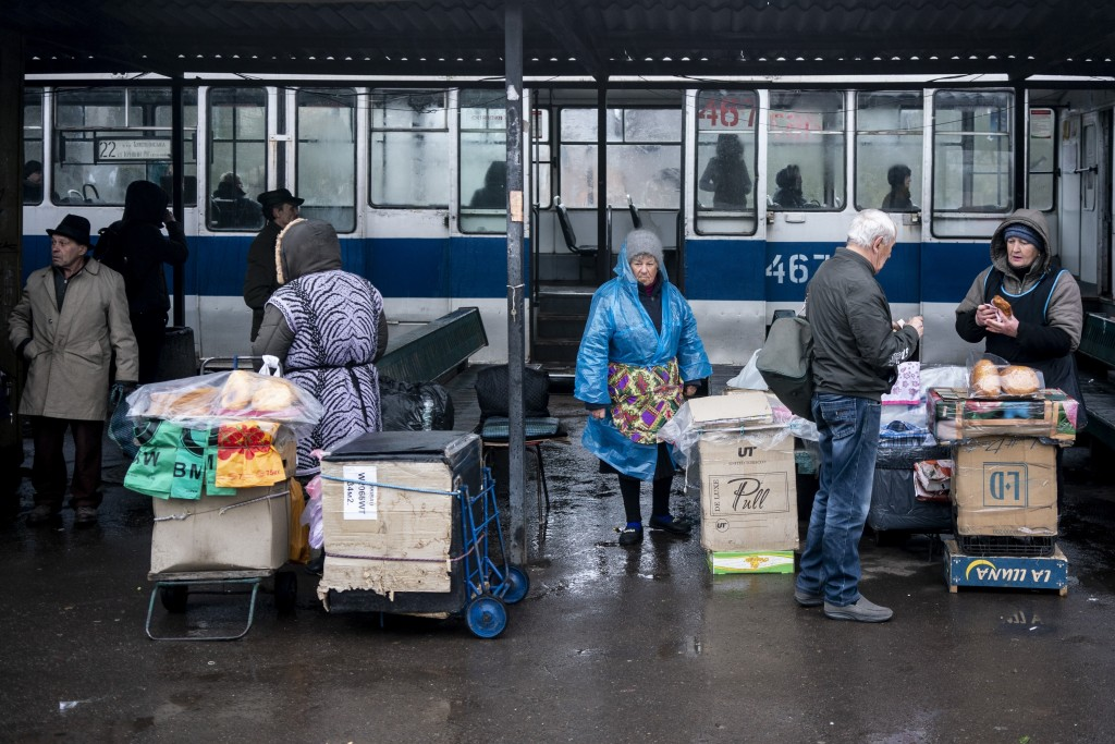 In this photo taken on Monday, April 15, 2019, women sell homemade meat patties at a railway station in Kryvyi Rih, in eastern Ukraine. The country vo...