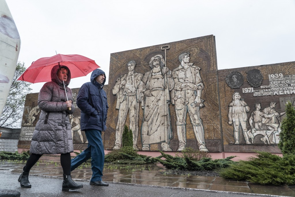 In this photo taken on Monday, April 15, 2019, people in Kryvyi Rih, an industrial city in eastern Ukraine, walk in front of a Soviet-era mosaic showi...