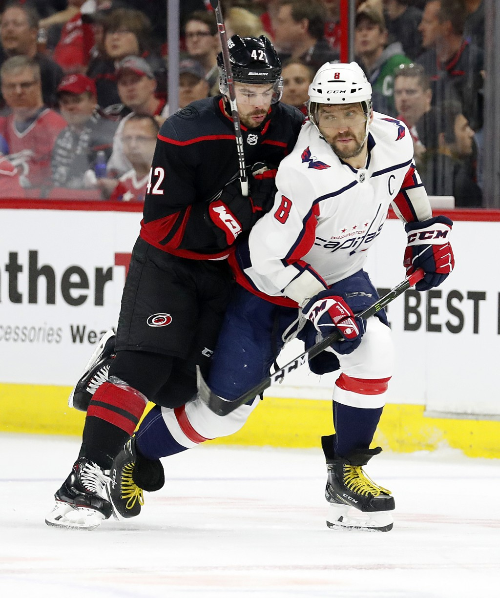 Washington Capitals' Alex Ovechkin (8), of Russia, tangles with Carolina Hurricanes' Greg McKegg (42) during the first period of Game 4 of an NHL hock